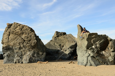 Young male on a large interesting shaped basalt sea stack on a Oregon Ocean beach photo