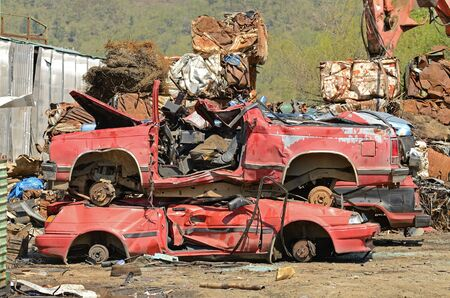 A stack of old red cars that have been through a primary crush at a metal recycling yard Reklamní fotografie