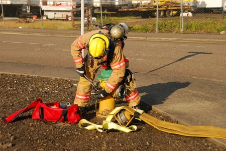 turnouts: Firefighers working at a potential fire in a industrial site Stock Photo