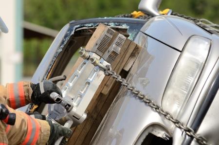 Les pompiers qui travaillent sur une désincarcération automobile avec un outil de sauvetage hydraulique