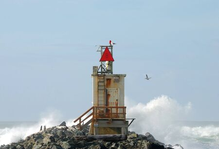 Light and horn beacon on the South Jetty of the Coquille River near Bandon Oregon photo