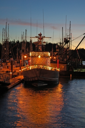 A fishing boat decorated for Christmas sits at dock