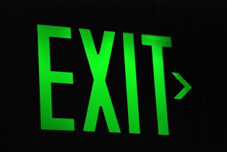 Green exit sign leads the way in the dark Standard-Bild