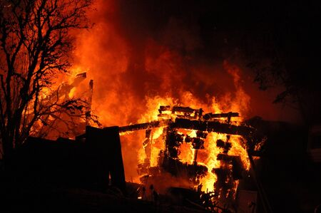 respond: Fire fighters respond to a winter residential structure fire at night Stock Photo