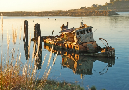 ship wreck: Mary D. Hume lying in the still waters of the Rogue River Bay near Gold Beach OR.  Boat originally built in 1881  Stock Photo