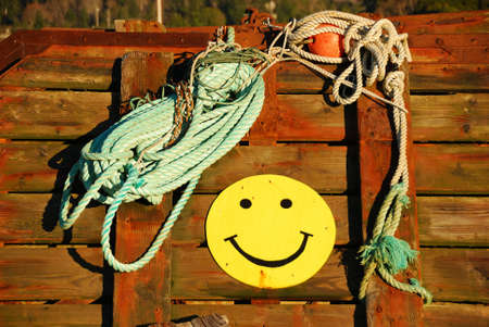 coiled: Smiley Face and coiled rope on a fishing boat deck being stored in the Port of Gold Beach Oregon at early morning