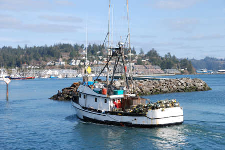 returning: Lillie M Returning from the Sea, Crabbing boat returing to harbor, Newport Bay, OR Stock Photo
