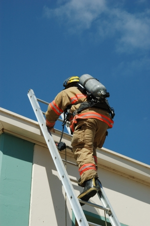 Fire fighter climbing a extension ladder to get to the top of a two story building photo