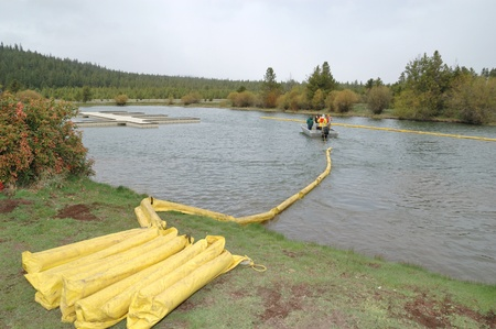 barrier: Small stream oil booming operation using small boats preventing the spread of hazardous materials,