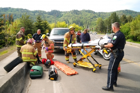 Packaging Up the Patient, minor injuries at a Single Motor Vehicle accident, Driver was adjusting stereo and lost control, SUV landed on sidewalk almost going over bridge to river, Stewart Parkway, Roseburg OR 新聞圖片