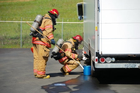Fire fighters making a on site recon of a truck leaking fluid,  The hazardous materials team trains on a recent corrosive drill in Roseburg Oregon  May 28, 2009 Stock Photo - 19075423