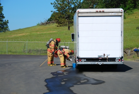 Fire fighters making a on site recon of a truck leaking fluid,  The hazardous materials team trains on a recent corrosive drill in Roseburg Oregon  May 28, 2009 Stock Photo - 19075422
