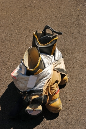 A pair of turnout bunker pants and boots sits after being taken off by a fire fighter Stock Photo
