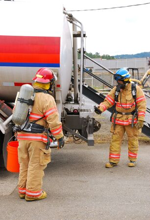 hazardous material team: Fire fighters making an entry at a Simulated flamable liquid leak at a bulk fuel facility during a haz mat team drill  Editorial
