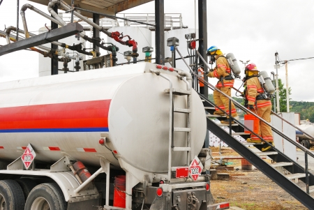 Fire fighters making an entry at a Simulated flamable liquid leak at a bulk fuel facility during a haz mat team drill