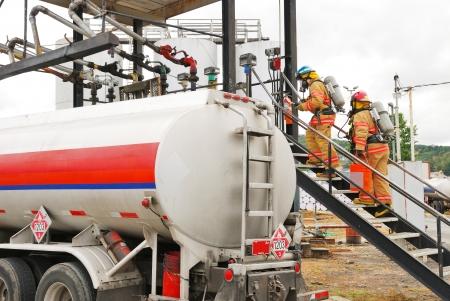 Haz マット中のバルク燃料施設でシミュレートされた引火性液体漏れにエントリを作る消防チーム ドリル 写真素材 - 19520000