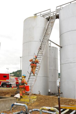 haz: Climbing the ladder up to the top of the above ground bulk storage tanks during a Simulated flamable liquid leak at a bulk fuel facility during a haz mat team drill  Editorial