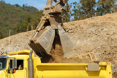 Excavator with clamshell bucket working a rock outcrop at a business development construction project in Roseburg Oregon