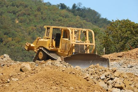 Large tracked bulldozer moving rock and dirt from a hill for a new commercial development photo