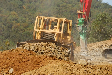 Large tracked excavator  using a hydraulic breaker or rock jack hammer on hard rock on a hill for a new commercial development photo