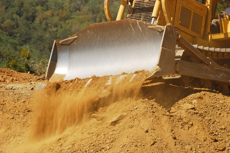 Large tracked bulldozer moving rock and dirt from a hill for a new commercial development