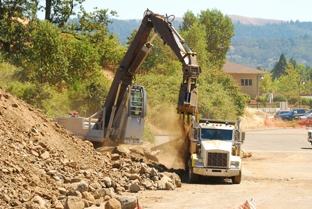 Clamshell bucket loader working a spoil pile on a hill removal project in Roseburg Oregon
