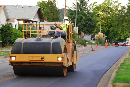 Large vibrating roller compactor working on an asphalt repaving project in Roseburg Oregon 版權商用圖片 - 20428160