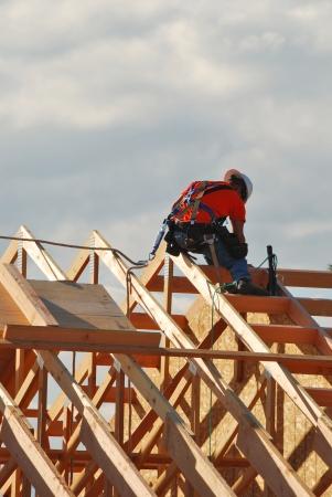 로즈버그, 오리건에 새 은행 건물에 대한 최종 지붕 서까래에 매는 노동자