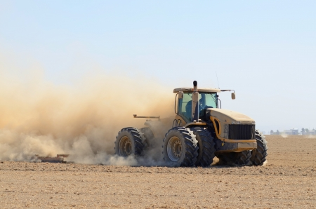 tractor pulling a disc soil finisher implement to smooth the soil after tillage and plowing Stock Photo - 20587394