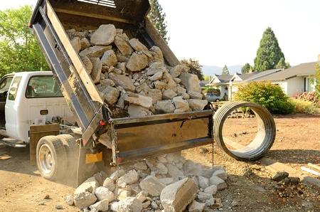 dumps: A small dump truck dumps concrete pieces during repair work following a broken water main leak from a fire hydrant base,