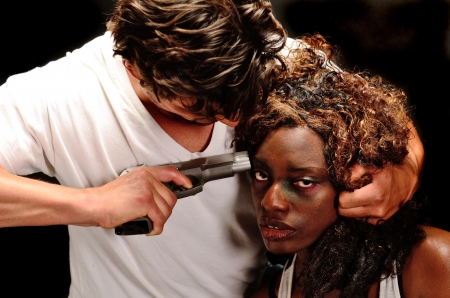 A young beautiful african american female and a handsom young white italian male pose showing domestic violence in this dark photo shoot against black 写真素材