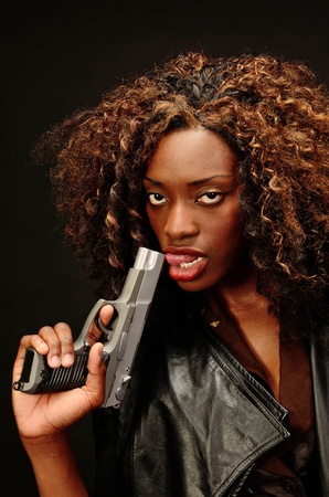 A young beautiful african american female holds a semi automatic pistol during this dark photo shoot against black Stock Photo - 20638218