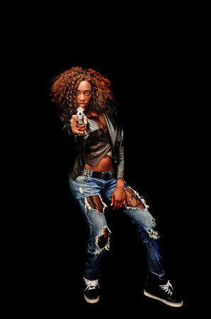 A young beautiful african american female holds a semi automatic pistol during this dark photo shoot against black Stock Photo - 20638198