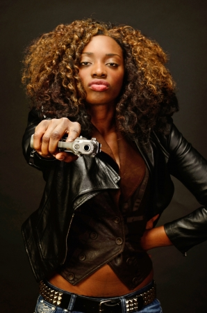 A young beautiful african american female holds a semi automatic pistol during this dark photo shoot against black Stock Photo - 20638210