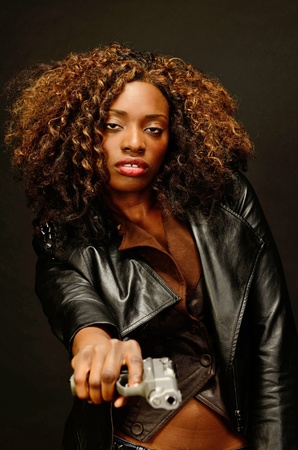 A young beautiful african american female holds a semi automatic pistol during this dark photo shoot against black Stock Photo - 20638217