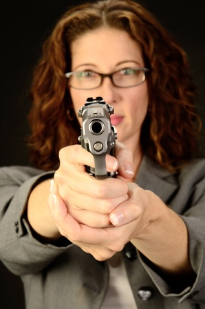 semi automatic: A middle aged, white, female business woman or teacher holds a semi automatic pistol during this dark photo shoot against black