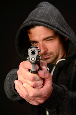 gritty: A young white, italian, male holds a semi automatic pistol during this dark photo shoot against black Stock Photo
