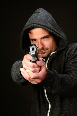 A young white, italian, male holds a semi automatic pistol during this dark photo shoot against black Stock Photo - 20638211