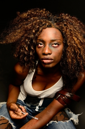 whore: A young beautiful african american female poses as a track whore shooting up narcotics in this dark photo shoot against black Stock Photo