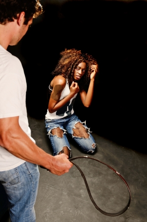 A young beautiful african american female and a handsom young white italian male pose showing domestic violence in this dark photo shoot against black Stockfoto