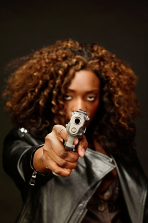 A young beautiful african american female holds a semi automatic pistol during this dark photo shoot against black Stock Photo - 20638222