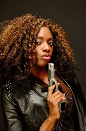 mujer con pistola: Una hermosa mujer afroamericana joven sostiene una pistola semi autom�tica durante esta sesi�n de fotos oscuro contra negro