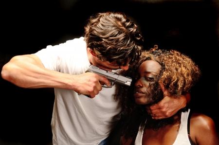 Een mooie jonge Afro-Amerikaanse vrouw en een knappe jonge witte Italiaanse mannelijke pose tonen huiselijk geweld in deze donkere fotoshoot tegen zwart