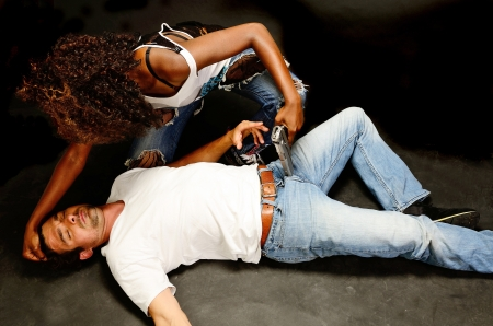 abused: A young beautiful african american female and a handsom young white italian male pose showing domestic violence in this dark photo shoot against black Stock Photo