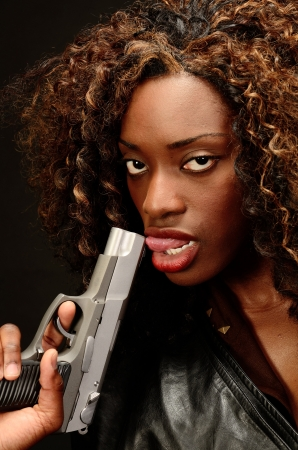 A young beautiful african american female holds a semi automatic pistol during this dark photo shoot against black Stock Photo - 20787417