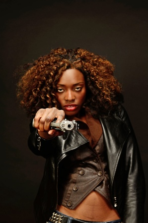 A young beautiful african american female holds a semi automatic pistol during this dark photo shoot against black photo