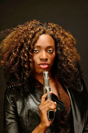 A young beautiful african american female holds a semi automatic pistol during this dark photo shoot against black Stock Photo - 20823740