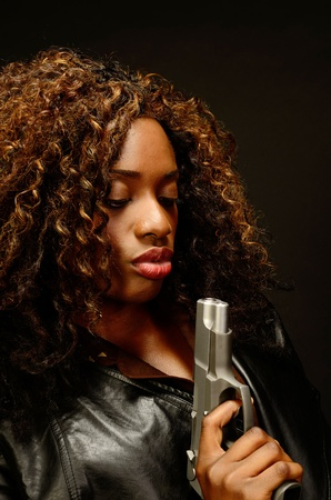 A young beautiful african american female holds a semi automatic pistol during this dark photo shoot against black Stock Photo - 20823757