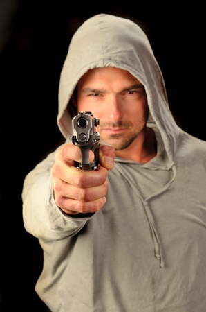 A young white, italian, male holds a semi automatic pistol during this dark photo shoot against black photo