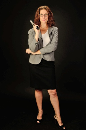 A middle aged, white, female business woman or teacher holds a semi automatic pistol during this dark photo shoot against black photo